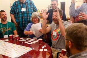 "ELM board member and Instigator Margaret Moreland leads the board game ""Beat the Eschaton - Full Inclusion Version"" board game created by Bennett Falk to tell the history of our movement. You can see this year's ""Kindle the Flame"" T-shirt on Andy Flatt (far left)."
