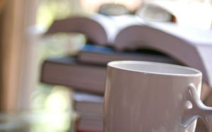 white-ceramic-coffee-cup-in-the-foreground-which-was-placed-in-front-of-a-stack-of-books-725x451